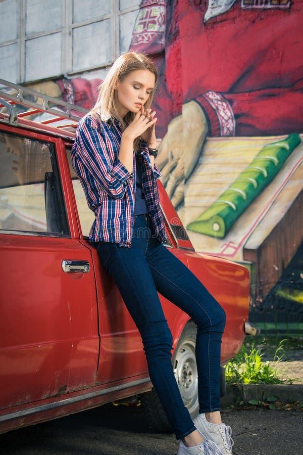 Het jonge aantrekkelijke model zit dichtbij de retro auto royalty-vrije stock foto's