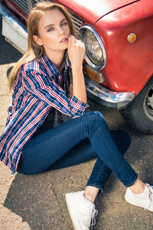 Het jonge aantrekkelijke model zit dichtbij de retro auto stock fotografie