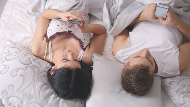 Het jonge aantrekkelijke paar die op het bed met smartphones samen liggen en rust hebben, iedereen kijkt in zijn telefoon stock foto's