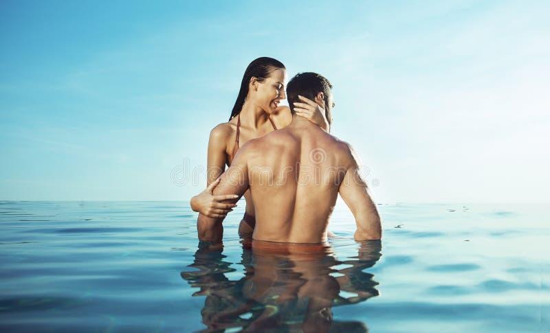 Het jonge, aantrekkelijke paar ontspannen in een warme, tropische pool royalty-vrije stock afbeeldingen