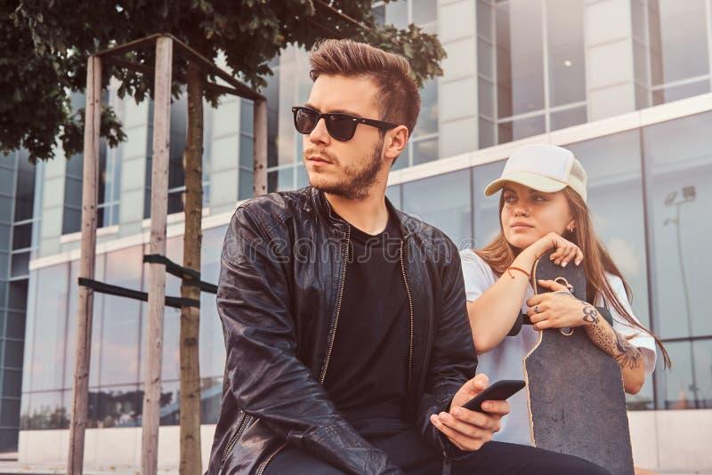 Het jonge aantrekkelijke paar zit op de de zomerstraat stock foto's