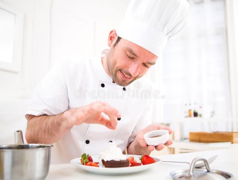 Het jonge aantrekkelijke professionele chef-kok koken in zijn keuken royalty-vrije stock afbeelding