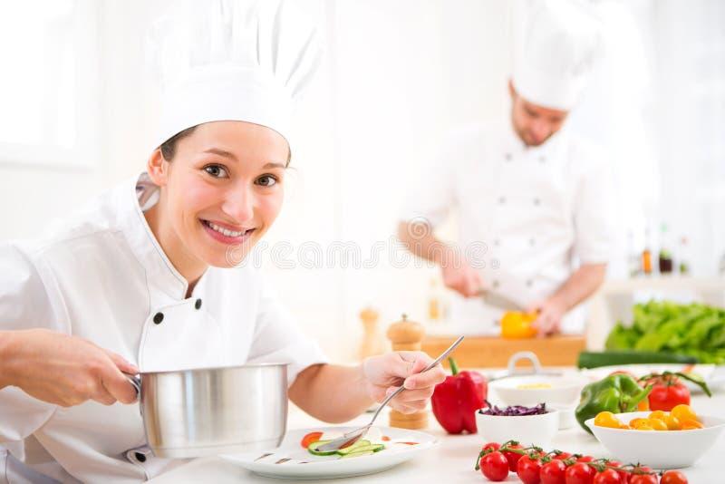 Het jonge aantrekkelijke professionele chef-kok koken in zijn keuken royalty-vrije stock foto's