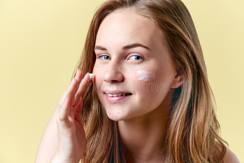 Het jonge aantrekkelijke roodharigevrouw van toepassing zijn moisturiser ziet room onder ogen, glimlachend en bekijkend camera Sc royalty-vrije stock afbeelding