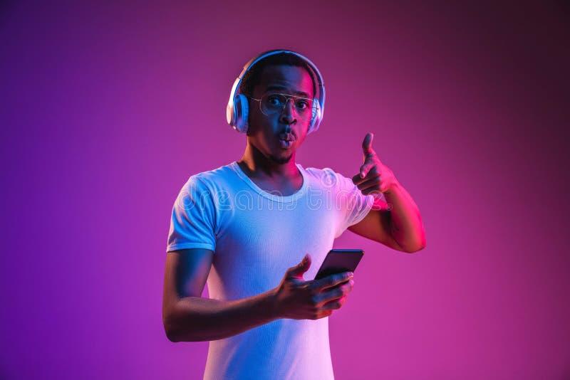 Het jonge Afrikaans-Amerikaanse man luisteren aan muziek in neonlicht royalty-vrije stock afbeeldingen