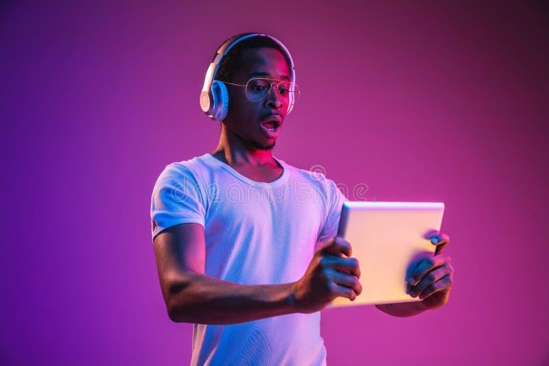Het jonge Afrikaans-Amerikaanse man luisteren aan muziek in neonlicht royalty-vrije stock fotografie