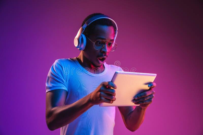Het jonge Afrikaans-Amerikaanse man luisteren aan muziek in neonlicht royalty-vrije stock afbeelding