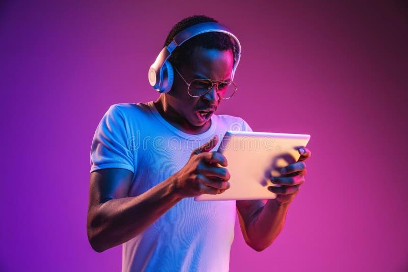 Het jonge Afrikaans-Amerikaanse man luisteren aan muziek in neonlicht stock afbeeldingen