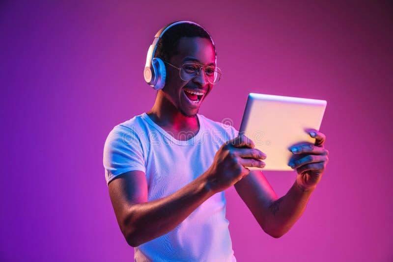 Het jonge Afrikaans-Amerikaanse man luisteren aan muziek in neonlicht stock afbeelding