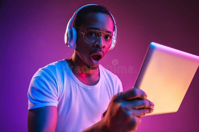 Het jonge Afrikaans-Amerikaanse man luisteren aan muziek in neonlicht stock fotografie