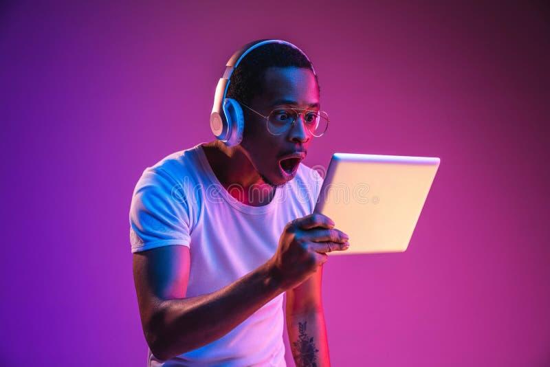 Het jonge Afrikaans-Amerikaanse man luisteren aan muziek in neonlicht royalty-vrije stock foto