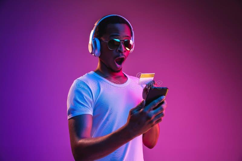 Het jonge Afrikaans-Amerikaanse man luisteren aan muziek in neonlicht royalty-vrije stock foto's