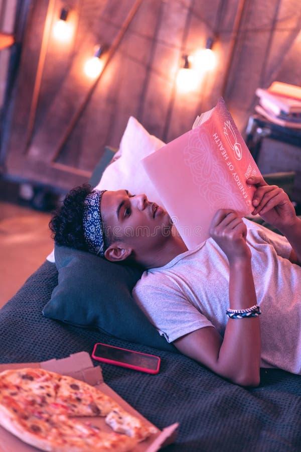 Het jonge Afrikaanse Amerikaanse boek die van de mensenlezing zelfs in bed bij nacht liggen royalty-vrije stock afbeelding