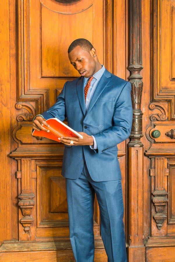 Het jonge Afrikaanse Amerikaanse boek van de Zakenmanlezing, die in Nieuw werken stock foto