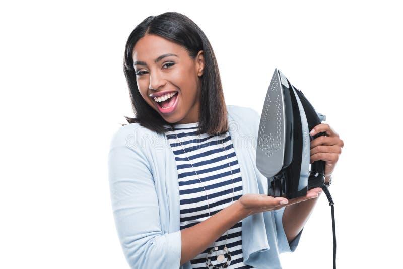 Het jonge Afrikaanse Amerikaanse die ijzer van de vrouwenholding op wit wordt geïsoleerd stock fotografie