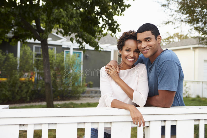 Het jonge Afrikaanse Amerikaanse paar omhelst buiten hun huis royalty-vrije stock foto