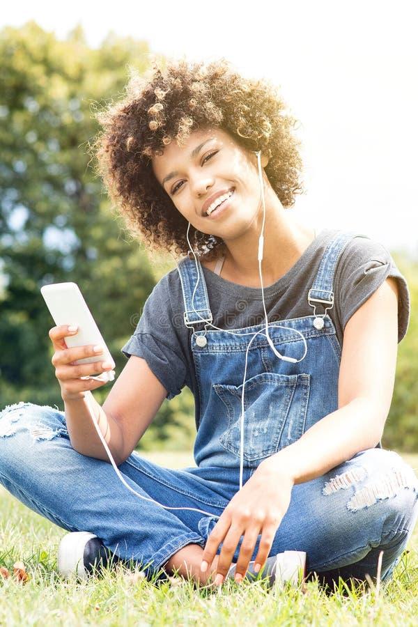 Het jonge Afrikaanse meisje ontspannen in park stock foto