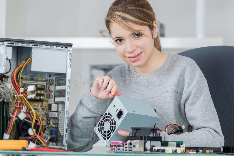 Het jonge apparaat van de de reparatieelektronika van de vrouwentechnicus stock afbeelding