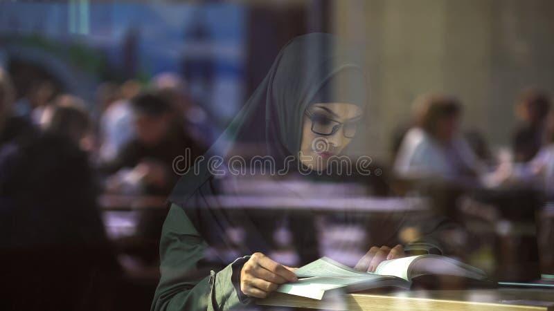 Het jonge Arabische boek van de damelezing in koffie, student die voor examens, literatuur voorbereidingen treffen stock afbeelding