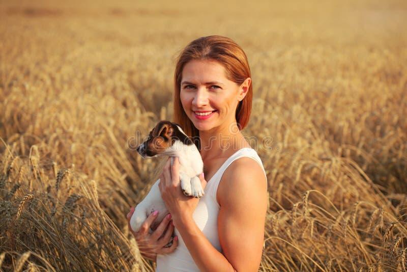 Het jonge atletische donkerbruine vrouw glimlachen, die Jack Russell houden terr stock foto's