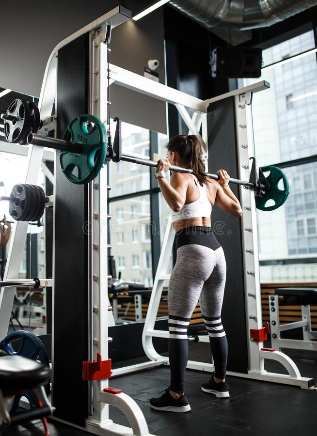 Het jonge atletische meisje kleedde zich in sportkledingshurkzit met een barbell in de moderne gymnastiek royalty-vrije stock afbeeldingen