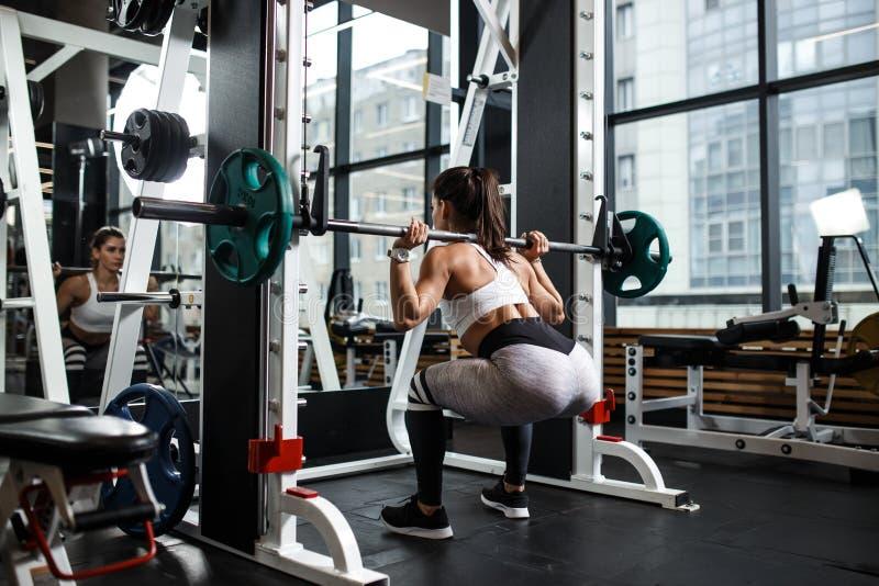 Het jonge atletische meisje kleedde zich in sportkledingshurkzit met een barbell in de moderne gymnastiek stock foto