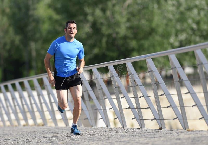 Het jonge atletische mens het praktizeren lopen en het sprinten op de stedelijke achtergrond van het stadspark in sport opleiding stock foto's