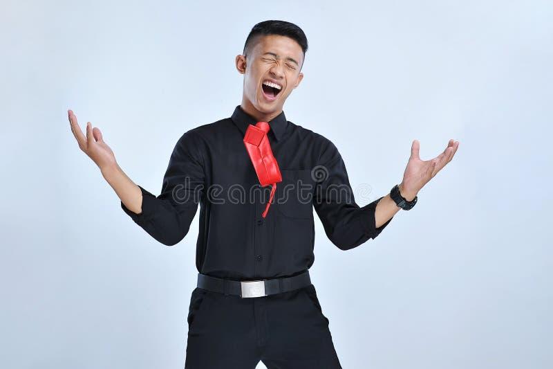 Het jonge Aziatische bedrijfsmens gelukkige en opgewekte vieren, uitdrukkend groot succes, schreeuwend het vieren, het winnen geb royalty-vrije stock afbeeldingen