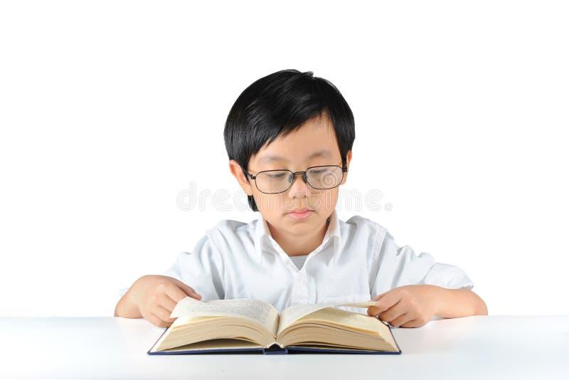Het jonge Aziatische boek van de schooljongenlezing stock foto's