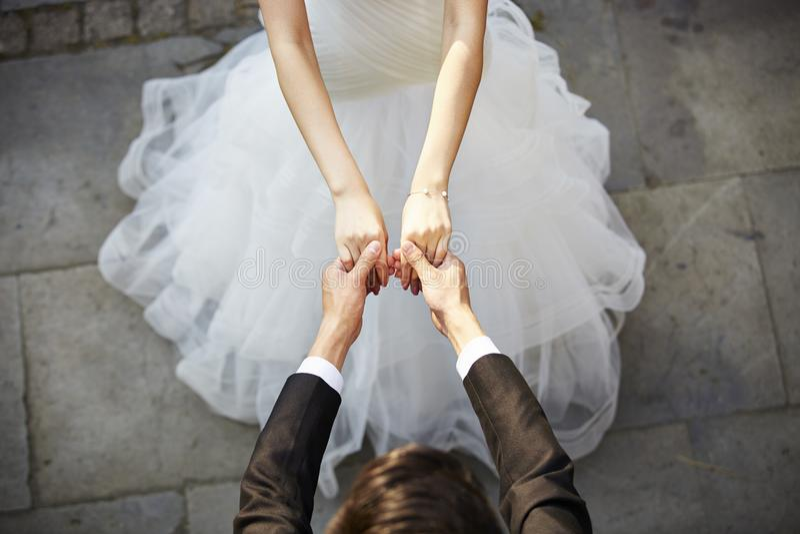 Het jonge Aziatische bruid en bruidegomholding handen en dansen royalty-vrije stock afbeeldingen