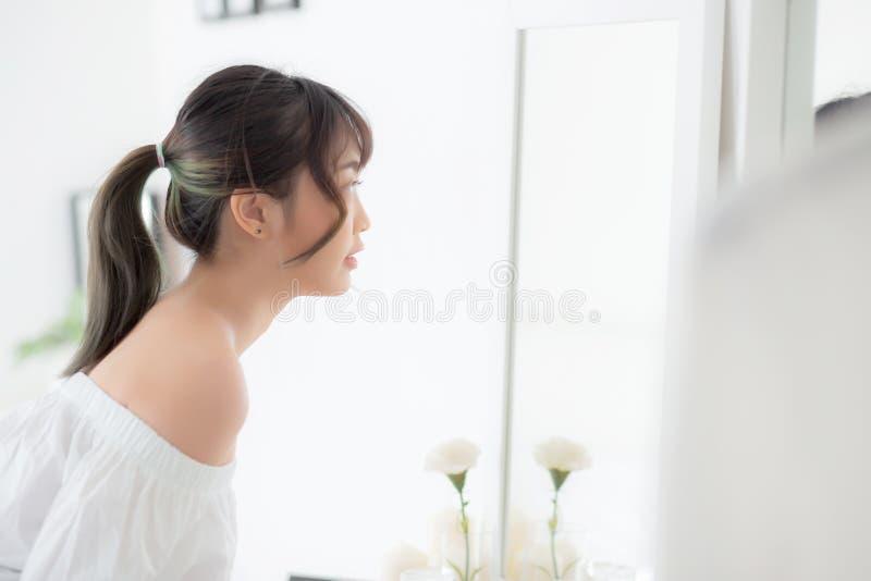 Het jonge Aziatische de vrouw van het schoonheidsportret bekijkt glimlachen Kaukasisch spiegel van het controleren van huidzorg m royalty-vrije stock afbeelding