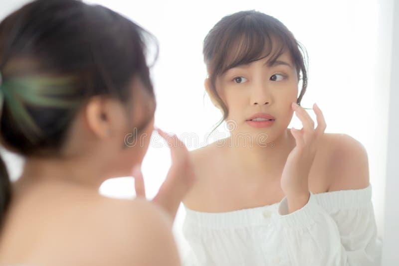 Het jonge Aziatische de vrouw van het schoonheidsportret bekijkt glimlachen Kaukasisch spiegel van het controleren van huidzorg m royalty-vrije stock fotografie