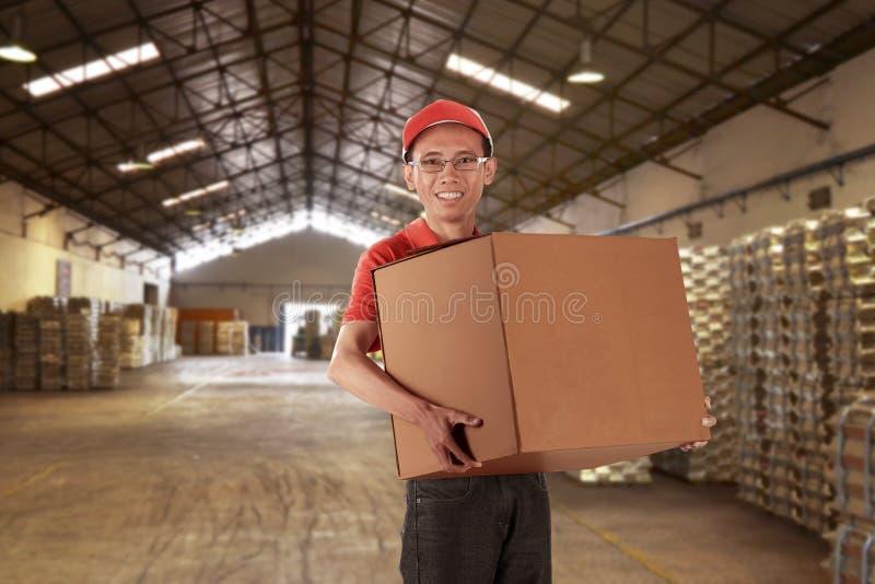 Het jonge Aziatische dragende pakket van de mensenkoerier royalty-vrije stock afbeelding