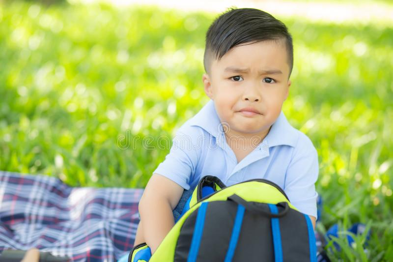 Het jonge Aziatische kind glimlachen en het openen rugzak in het gazon, pret van de het jonge geitje de leuke uitdrukking van Azi stock afbeeldingen