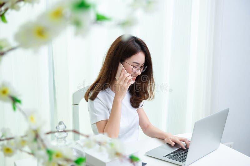 Het jonge Aziatische meisje is freelancer thuis met haar particuliere sector stock afbeelding