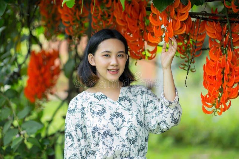 Het jonge Aziatische meisje geniet van met bloemen stock afbeeldingen