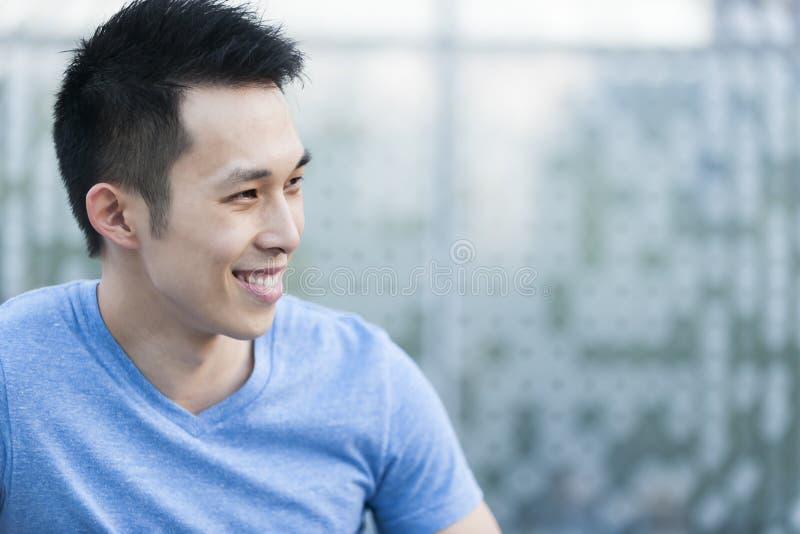 Het jonge Aziatische mens glimlachen stock afbeelding