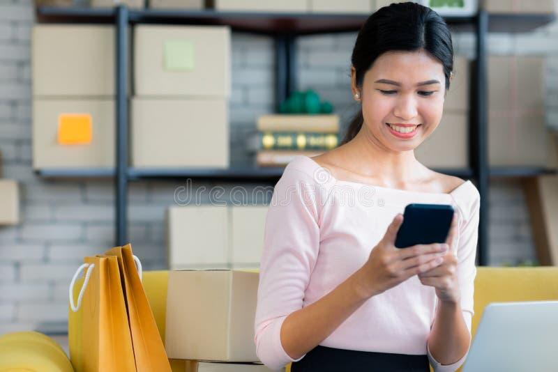 Het jonge Aziatische mooie meisje is het gelukkige glimlachen aan het winkelen online w stock afbeeldingen