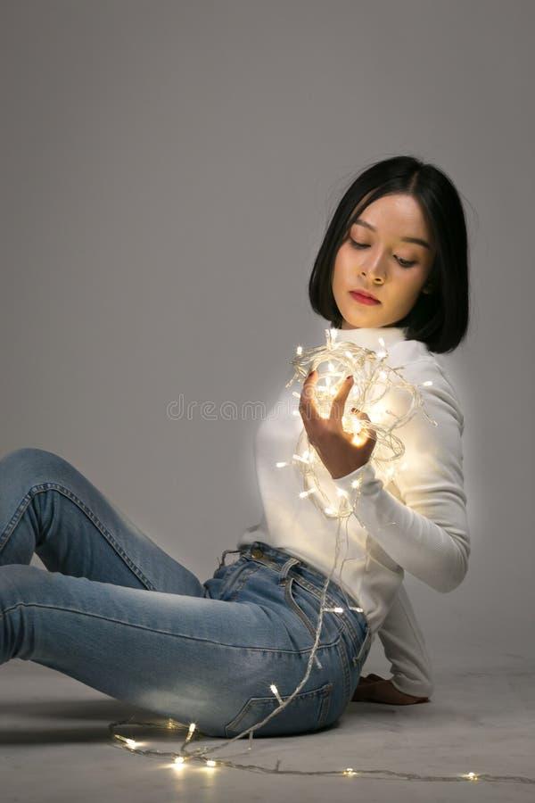 Het jonge Aziatische mooie meisje spelen met geleid licht stock afbeeldingen