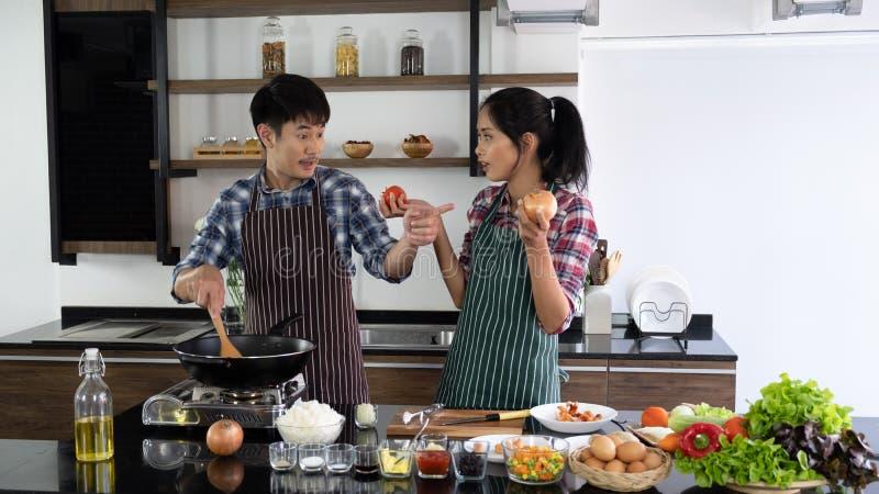 Het jonge Aziatische paar is gelukkig samen te koken, helpen twee families elkaar voorbereidingen treffen om in de keuken te koke royalty-vrije stock afbeelding
