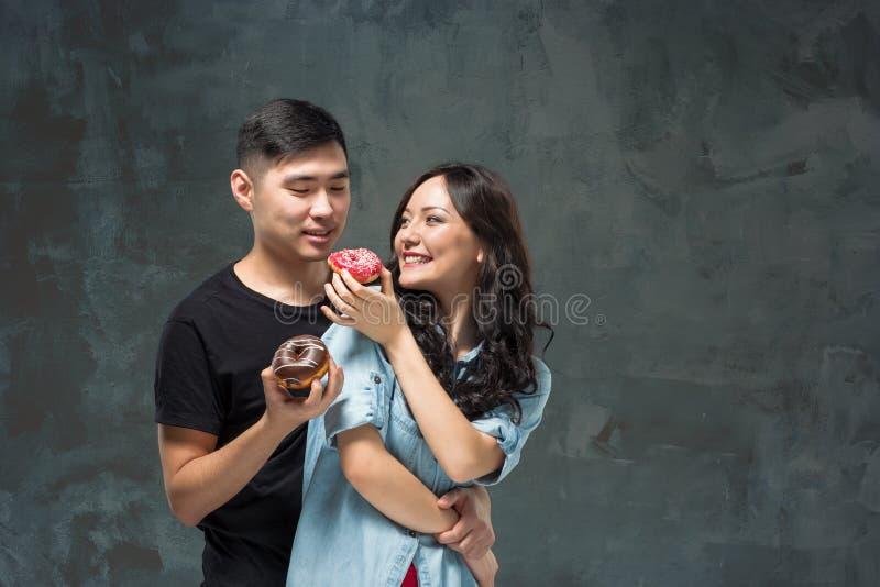 Het jonge Aziatische paar geniet van het eten van zoete kleurrijke doughnut stock foto's