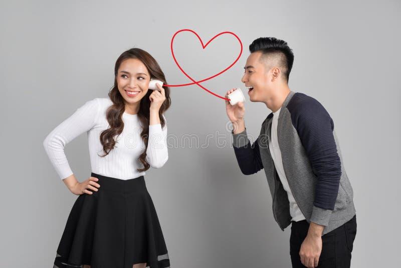 Het jonge Aziatische paar met kan telefoneren geïsoleerd op grijze achtergrond stock fotografie