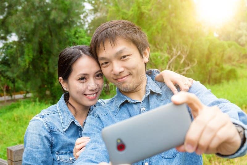 Het jonge Aziatische paar neemt selfie in park royalty-vrije stock foto's