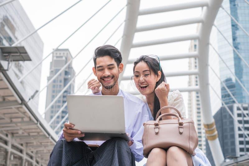 Het jonge Aziatische paar zit gebruikend laptop met opgewekt en vrolijk stock foto
