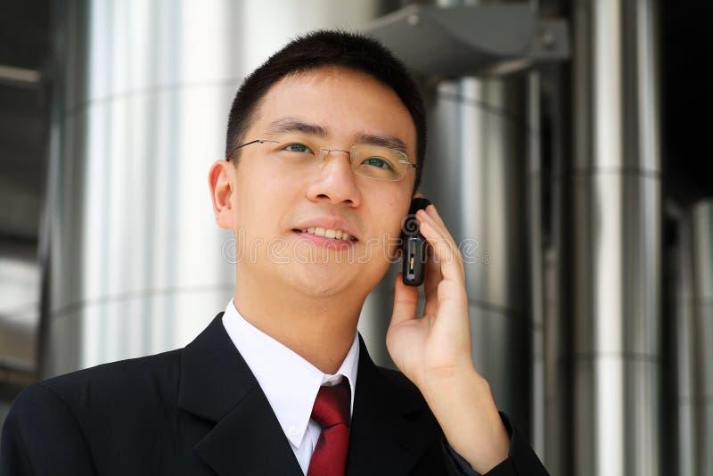 Het jonge Aziatische uitvoerende spreken op handphone royalty-vrije stock fotografie