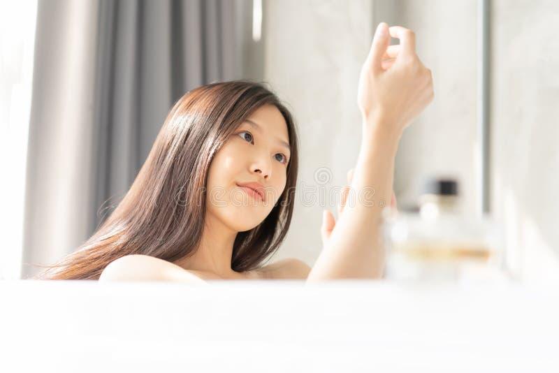 Het jonge Aziatische vrouw ontspannen in een bad stock fotografie