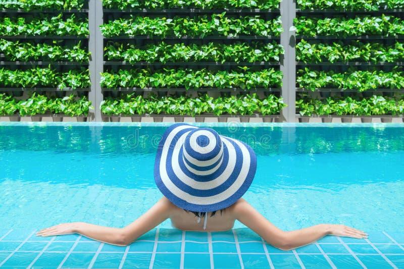 Het jonge Aziatische vrouw ontspannen in zwembad bij kuuroordtoevlucht Ontspannend concept De vrouwen ontspannen bij poolside royalty-vrije stock afbeelding