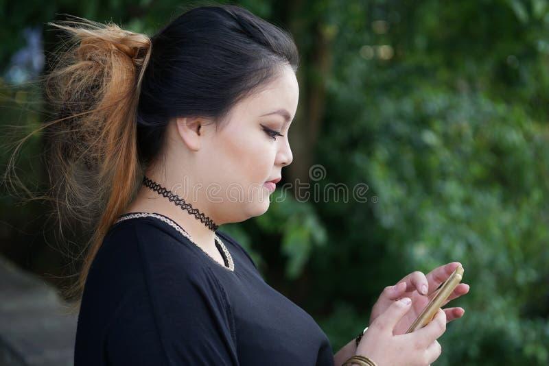 Het jonge Aziatische vrouw texting met smartphone royalty-vrije stock afbeeldingen