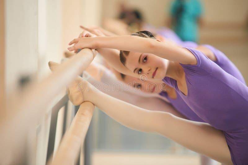 Het jonge ballerina uitrekken zich vóór balletpraktijk stock foto