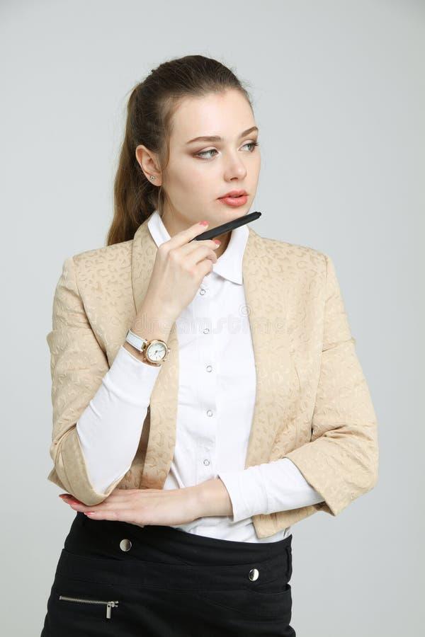 Het jonge bedrijfsvrouw denken, die pen in hand houden stock afbeelding